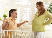 Parents laughing at each other, father fixing baby bed, gesturing, raising arms at pregnant mother with hands on waist.?