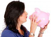 Woman cherishing her savings giving a kiss to the piggybank