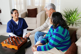 image of health-care  - Home health care worker and an elderly couple playing game - JPG