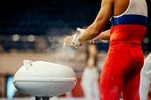 Gymnast Rubs Chalk On His Hands At Gymnastics Exercises On Horizontal Bar poster