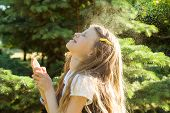 Little Girl Spraying Face With Thermal Water. Joy And Enjoyment On A Hot Sunny Day. poster