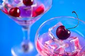 Cherry Cocktail Close-up. Martini Glass With Ice Cubes And Cherries On A Bright Blue Background With poster