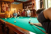 Young Smiling Men And Women Playing Billiards At Office Or Home After Work. Business Colleagues Invo poster