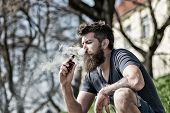 Bearded Man Smokes Vape On Sunny Day. Relaxation Concept. Man With Long Beard And Clouds Of Smoke Lo poster