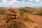 Cairn Built On Top Of A Hill Under A Cloudy Sky Next To A Footpath With A View Into The Distance In  poster