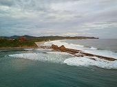 Magnific Rock Beach In Nicaragua. Surfers In Magnific Rock Bay In Nicaragua poster