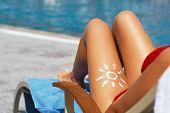Young Woman With Sun Shape On The Leg Holding Sun Cream Bottle On The Beach. Sun Protection Sun Crea poster