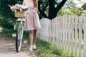 Partial View Of Woman In Dress With Retro Bicycle With Wicker Basket Full Of Flowers At Countryside poster