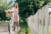 Young Beautiful Woman In Dress With Retro Bicycle With Wicker Basket Full Of Flowers At Countryside poster