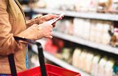 Woman In Supermarket Aisle With Food Shelf Reading Shopping List And Holding Basket. Woman Buying Gr poster