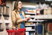 Woman With Shopping List In Supermarket And Grocery Store. Happy Customer Doing Groceries With Budge poster