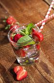 Summer Cold Drink With Strawberries, Mint And Ice In Glass On Wooden Background. Closeup Of Cocktail poster