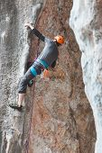 A Man In Helmet Climbs The Rock. poster