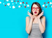 Portrait Of Beautiful Surprised Young Woman In Glasses On The Wonderful Blue Studio Background And A poster