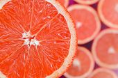 Top View Of A Fragment Of The Red Grapefruit Slice On The Background Of Many Blurred Grapefruit Slic poster