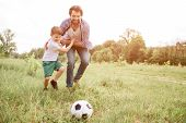 Father Is Playing Football With His Son. They Are Running Down The Meadow. Boy Is Hugging His Dad An poster