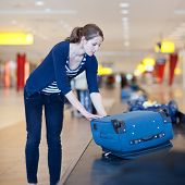 Baggage reclaim at the airport - pretty young woman taking her suitcase off the baggage carousel (co