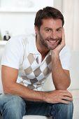 Homem sorridente relaxando em sua sala de estar