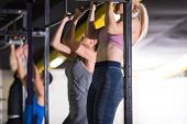 group of young muscular athletes doing pull ups on the horizontal bar as part of Cross fitness Train poster