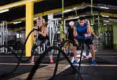 young fit sports couple working out in functional training gym doing  battle ropes cross fitness exe poster