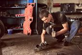 Auto Mechanic Squatting Working On Car Detail On Floor With Hammer Helping At Auto Repair Shop. Stro poster