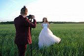 Wedding Couple At A Photo Shoot In A Wheat Field. The Groom In A Red Suit Shoots The Bride On The Ca poster