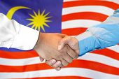 Business Handshake On Malaysia Flag Background. Men Shaking Hands And Malaysia Flag On Background. S poster