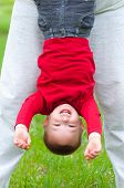 Cute happy little boy hanging upside down over the grassy meadow on beautiful spring day