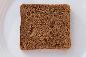 Slice Of Brown Bread With Raisins On A White Plate Top View. A Square Slice Of Rye Bread On A Plate. poster