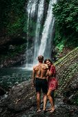 A Beautiful Girl Embraces A Man Of Athletic Build At The Waterfall. Honeymoon Trip. A Couple In Love poster