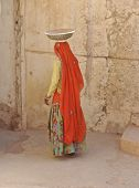 stock photo of rajasthani  - Woman at Amber Fort in traditional Rajasthani clothing and carrying dish on her head - JPG