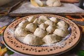Raw Dumplings Are Laid On A Prepared Plate For Further Preparation. poster