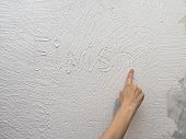 Finger Paints A Sign finish  On A White Stucco Wall. poster