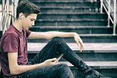 Young man  sits on the ladder  with smartphone and earphones,  in the street.  Teenage boy is using  poster