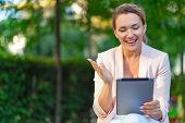 Smiling businesswoman with a tablet in the park. Successful  businesswoman is using tablet, outdoors poster