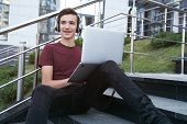 Smiling teenage boy with laptop on the street. Handsome young man works on a notebook, outdoors. Che poster
