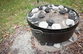 foto of dutch oven  - Cooking dinner in the dutch oven using charcoals to heat it