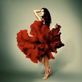 beautiful romantic girl in red flower dress with long broun hair barefoot, full length studio portrait