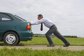 Businessman Pushing A Car