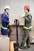 stock photo of jack-in-the-box  - Two foremen lifting cardboard box at warehouse - JPG