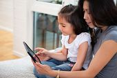 stock photo of mums  - Mother and daughter reading electronic book at home - JPG