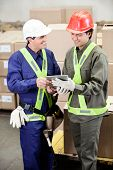 Happy young foremen using digital tablet in warehouse