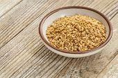 Gold Flussmittel Samen in einer kleinen Keramikschale gegen eine Grunge-Holz-Oberfläche