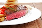 meat food : roast beef fillet mignon served on white plate with tomatoes , potatoes , and chives on wooden table