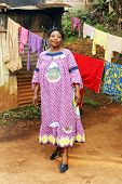 picture of overpopulation  - Pregnant black African woman in her backyard with clothesline - JPG