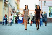 foto of crowd  - two elegant women walking the crowded city with shopping bags - JPG