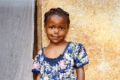 stock photo of little black dress  - Portrait of a cute and sweet little black African girl smiling but looking a bit shy posing in front of her house - JPG