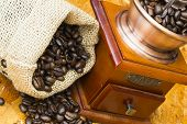 picture of scrotum  - fresh roasted coffee beans in a small scrotum and old wooden manual coffee grinder - JPG