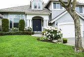 image of garage  - Horizontal photo of modern home in North American Suburbs with plush green grass rhododendron and tulips flower in mid spring season - JPG