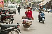 Woman Carrying Baskets On The Street. Hanoi. Vietnam.